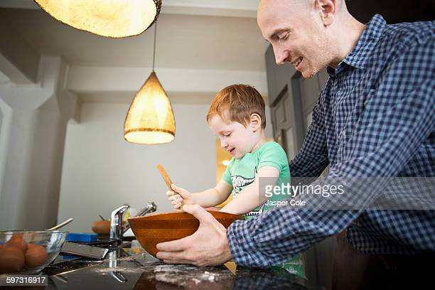 Father teaching son to cook in kitchen