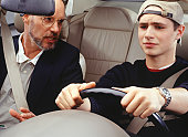 Father teaching son to drive car