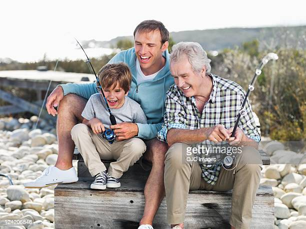 Father teaching son to fish, grandfather looking on