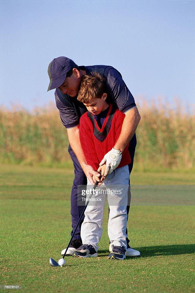 Father teaching son to golf : Stock Photo