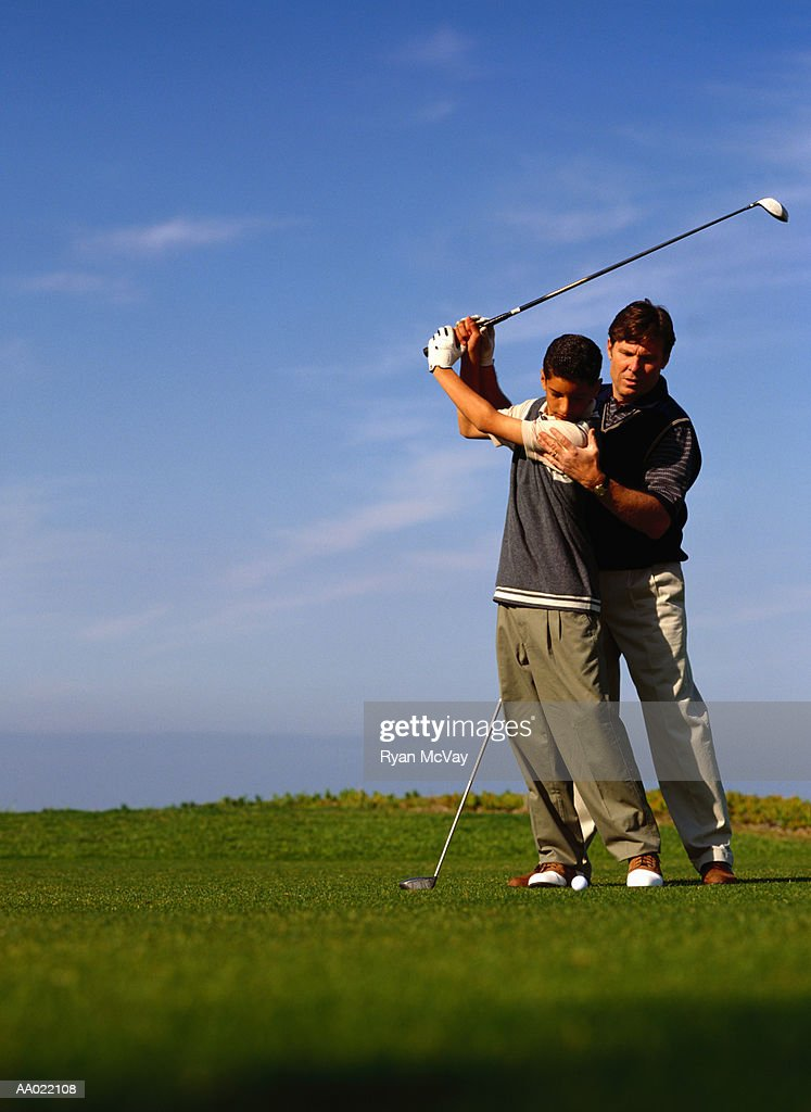 Father Teaching Son to Play Golf : Stock Photo