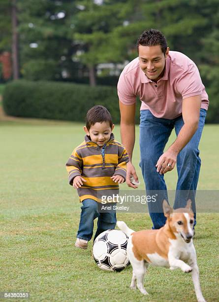 Father Teaching Son to Play Soccer with Dog