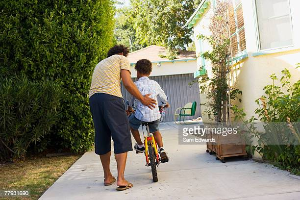 Father teaching son to ride bicycle in driveway