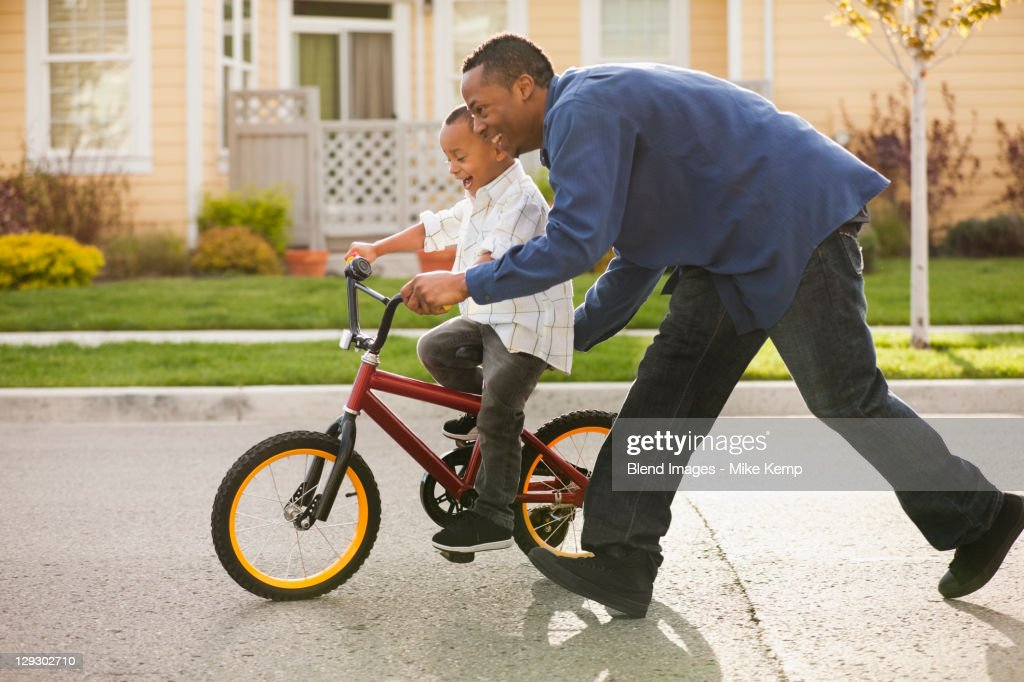 Father teaching son to ride bicycle