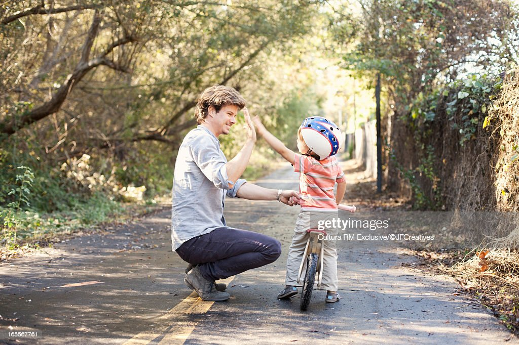 Father teaching son to ride bicycle : Stock Photo