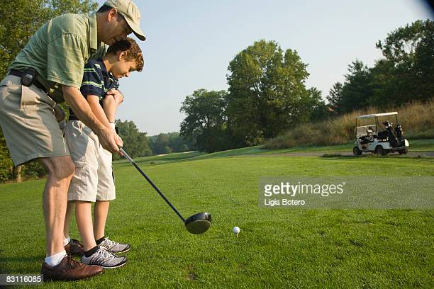 Father teaching son to swing golf club