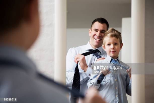 Father teaching son to tie a tie