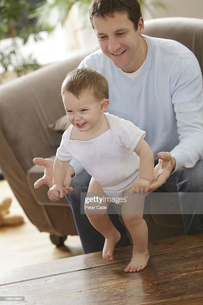father teaching son to walk : Stock Photo