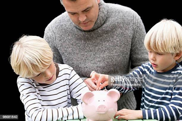 Father teaching sons to save