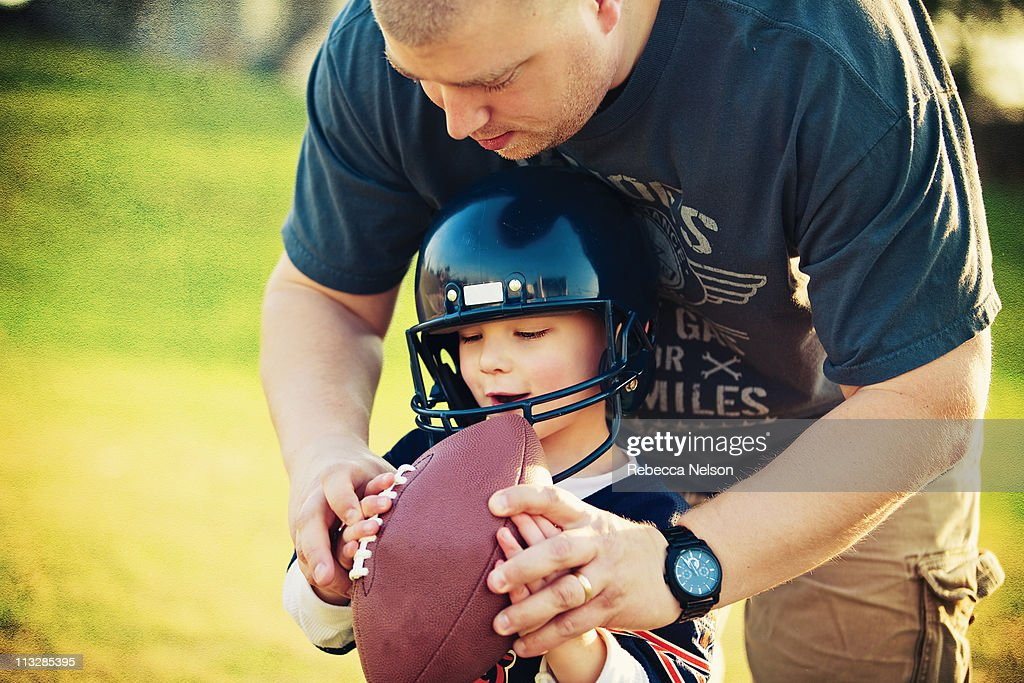 Father teaching young son how to hold a football : Stock Photo