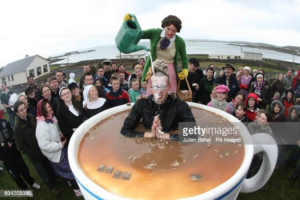 Father Ted fan Peran Odges sitting in a giant cup of tea with Mrs Doyle pouring milk over him during the Father Ted Festival on the Aran Islands