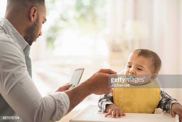 Father texting on cell phone and feeding baby son