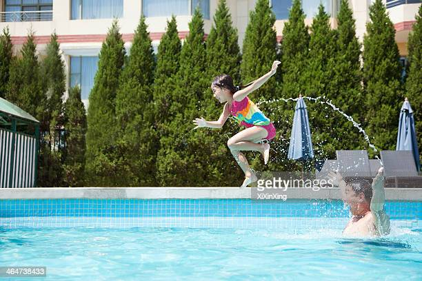 Father throwing daughter into the pool, mid-air