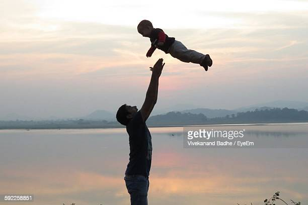 Father Throwing Son In Air By Lake Against Sky During Sunset