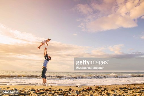 Father throwing young girl (2-3) in to air on beach