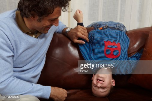 Father tickling his son on couch