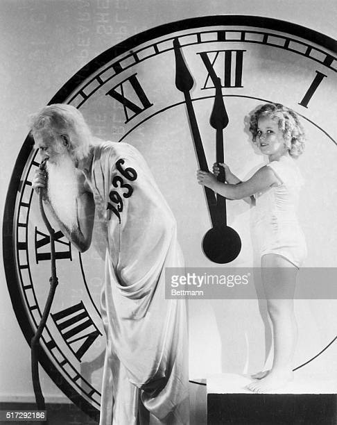 Father Time is about ready to take his annual runout powder and this year Shirley Temple as apparently been choosen to give him the air She is shown...