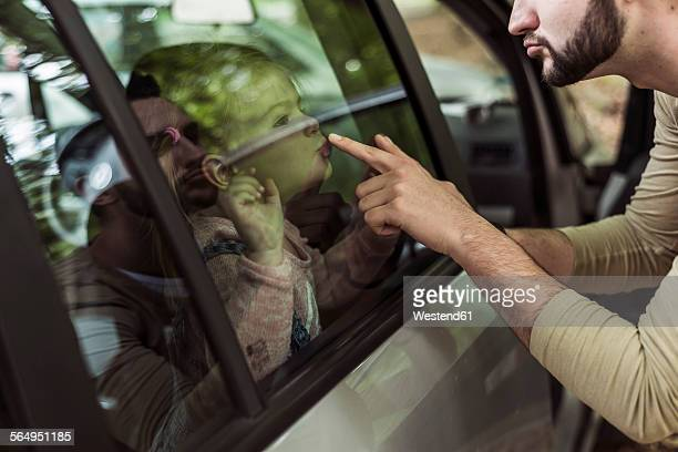 Father touching girls mouth behind car window
