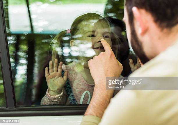 Father touching girls nose behind car window