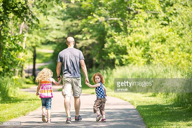 Father & Two Daughters Walking Through Wooded Park Trail