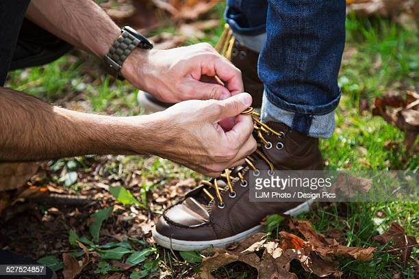 Father tying his son's hiking boots in a park