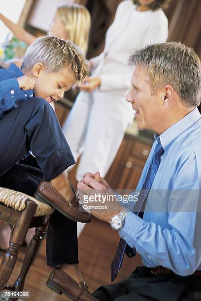 Father tying son's shoe