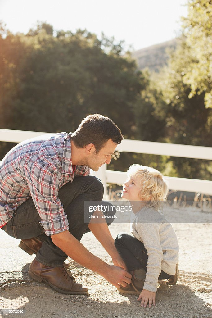 Father tying son's shoelaces : Stock Photo