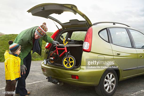 Father unloading bicycle from car