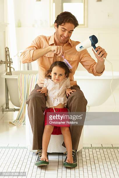 Father using hair dryer on daughter (2-4), portrait of girl
