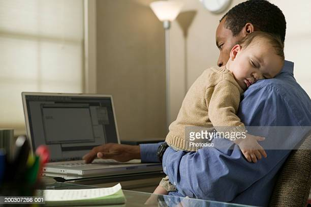 Father using laptop, holding son (9-12 months) on shoulder in home office
