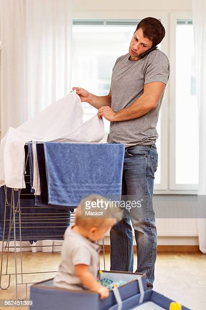 Father using mobile phone while drying clothes with baby boy playing at home