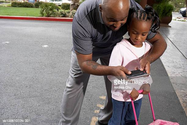 Father using palmtop with daughter (4-5 years) on driveway