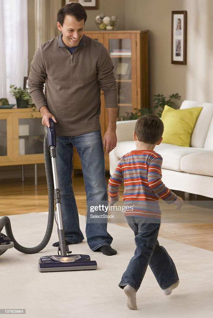 Father vacuuming with son watches : Stock Photo