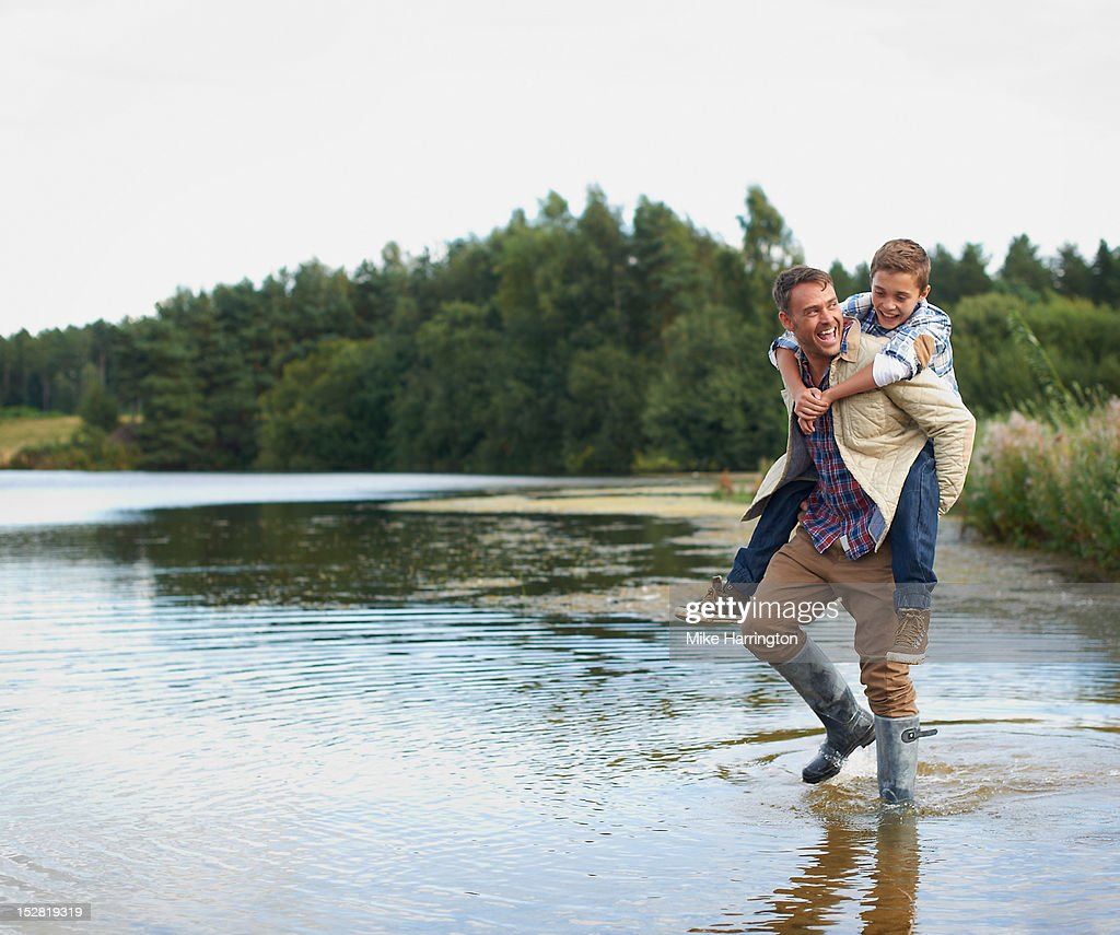 Father wading in lake, giving son piggyback. : Stock Photo