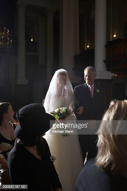 Father walking bride down church aisle, smiling