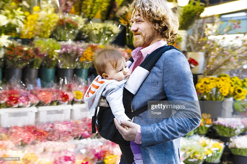Father walking through city with baby : Stock Photo