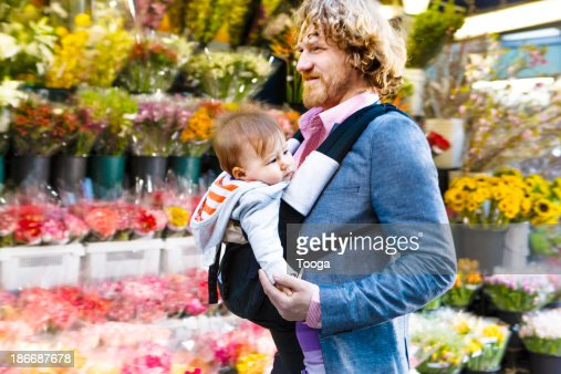Father walking through city with baby