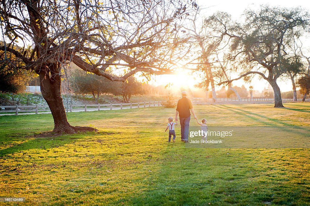 Father walking with son and daughter in sunlit field : Stock Photo