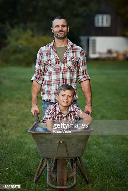 Father walking with son sitting in wheelbarrow