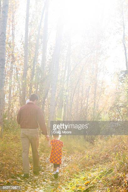 A father walks with his two daughters during a fall family portrait session in Kalispell, Montana.