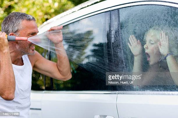 Father washing car and playing with daughter