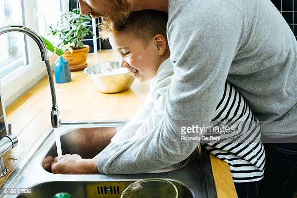 Father Washing Sons Hands In Kitchen Sink After Cooking Together