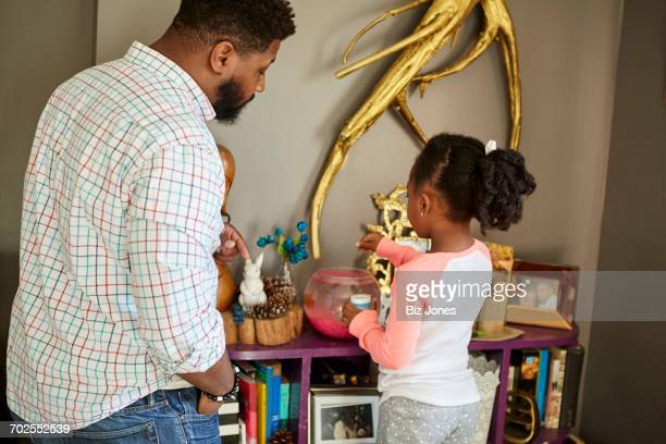 Father watching daughter feed fish in goldfish bowl