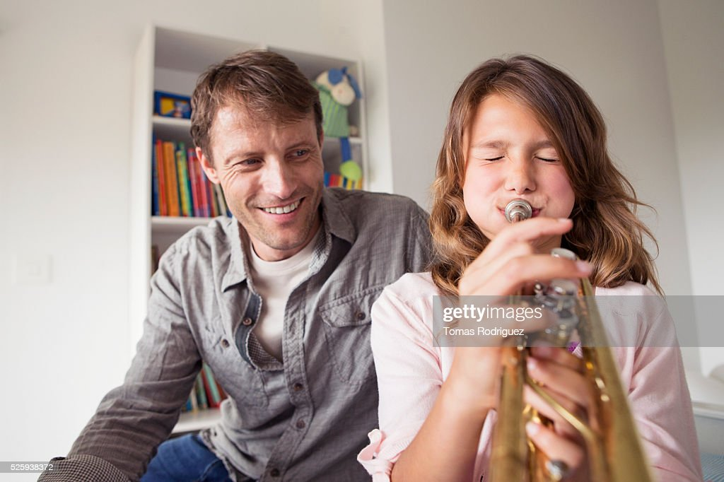 Father watching daughter (8-9) playing trumpet : Stock Photo