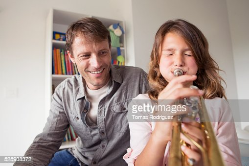 Father watching daughter (8-9) playing trumpet : Stock-Foto