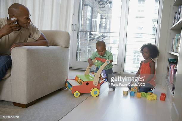 Father watching his son and daughter play