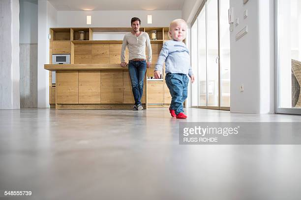 Father watching male toddlers walking on dining room floor