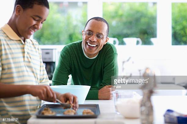 Father Watching Son Bake Cookies