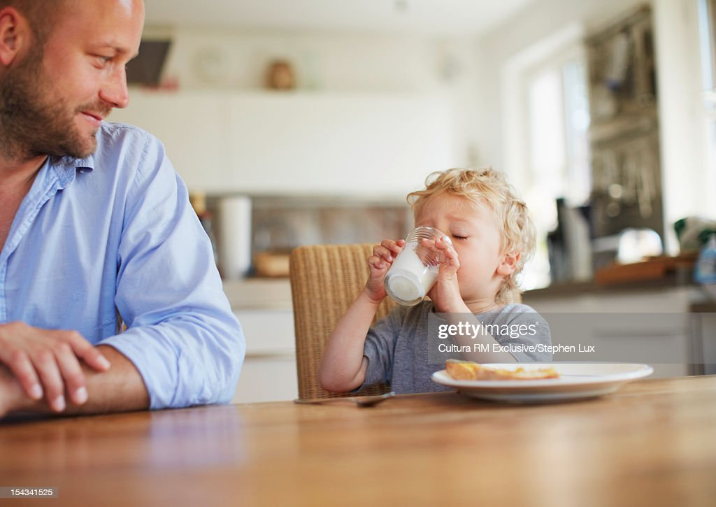 Father watching son drink milk at table