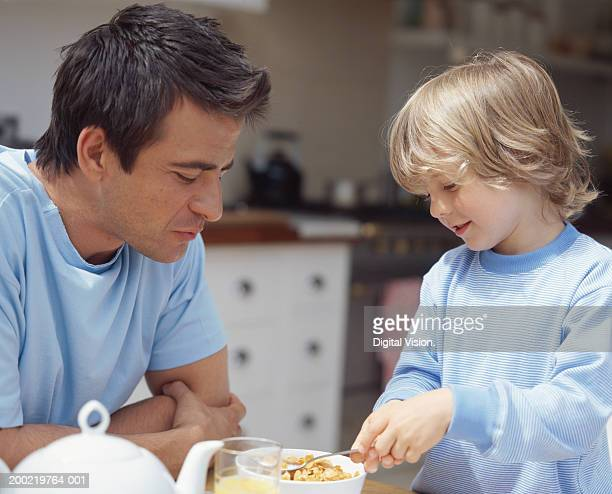 Father watching son (4-6) having breakfast cereal